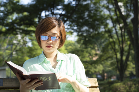 autodidact: serious young, beautiful girl holding an open book, read background summer green park