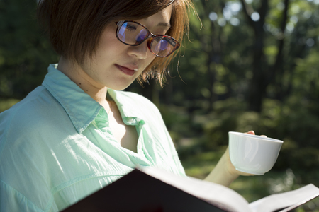 Girl reading a book in park, woman, green Stock Photo