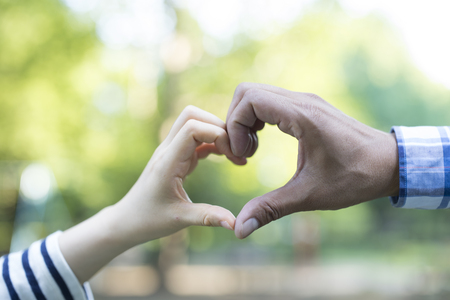 Shiloutte of two hands join to form a heart shape with sun beam inside the heart Banque d'images