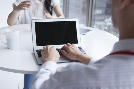 Businesspeople working together in bright office, sitting at desk.