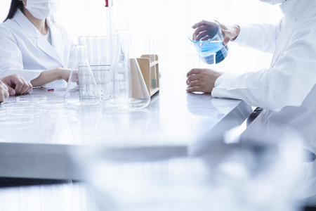 Young scientists in white uniform working in laboratory 写真素材