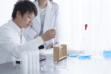 Science, chemistry, technology, biology and people concept-young scientists with test tube and microscope making research in clinical laboratory and taking notes