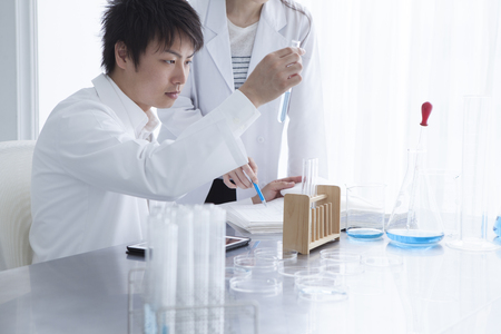 laboratorian: Science, chemistry, technology, biology and people concept-young scientists with test tube and microscope making research in clinical laboratory and taking notes