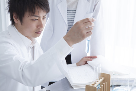 causasian: Science, chemistry, technology, biology and people concept-young scientists with test tube and microscope making research in clinical laboratory and taking notes