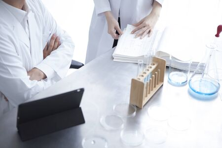 causasian: Science, chemistry, technology, biology and people concept-young scientists with pipette and test tube making research in clinical laboratory Stock Photo