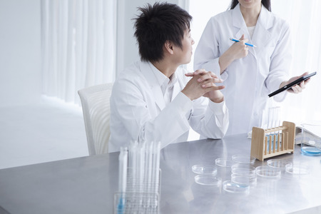 causasian: Scientist team pouring chemicals in a laboratory Stock Photo