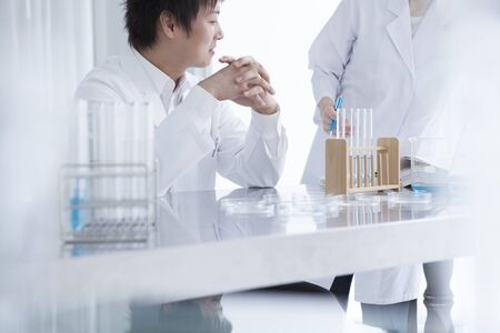 Scientist team pouring chemicals in a laboratory 写真素材