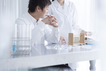 Scientist team pouring chemicals in a laboratory Stock Photo