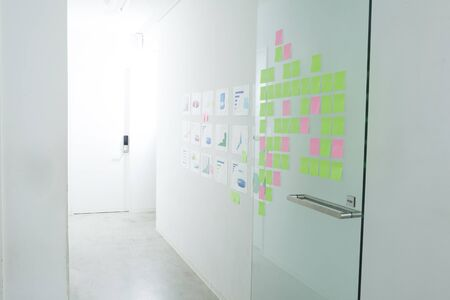 glass door: A lot of sticky notes that are attached to the wall of the office