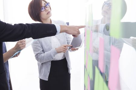 asian business man: Businessmen are talking while watching the material that is attached to the office of the board Stock Photo