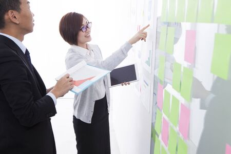drawing a plan: Business people discussing ideas with adhesive notes in office Stock Photo