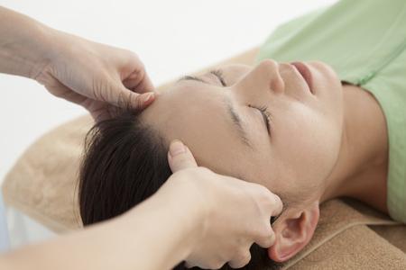 acupuntura china: Mujer atractiva adulta recibir masaje de cabeza