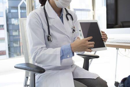 described: Women doctors are described in a patient using a tablet computer