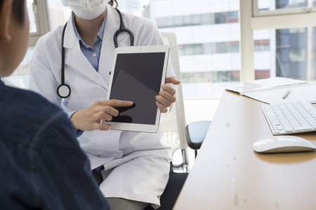 Pediatricians have a description using the tablet to a boy in the clinic