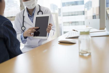 Kinderartsen hebben een beschrijving met behulp van de tablet aan een jongen in de kliniek