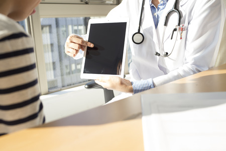 describes: Doctor describes the symptoms by using the tablet to boy Stock Photo
