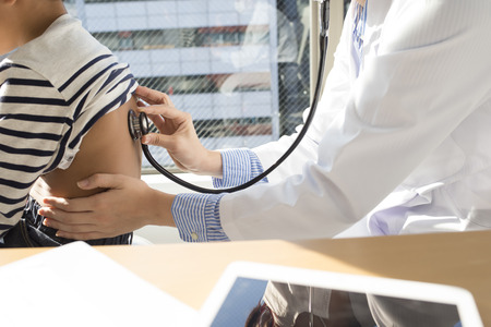 Female doctor looking at the stethoscope a boy in examination room Imagens