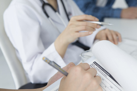 white coat: Young nurse to fill out the patient data Stock Photo