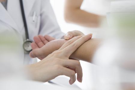 Vrouw arts om de pols te meten Stockfoto
