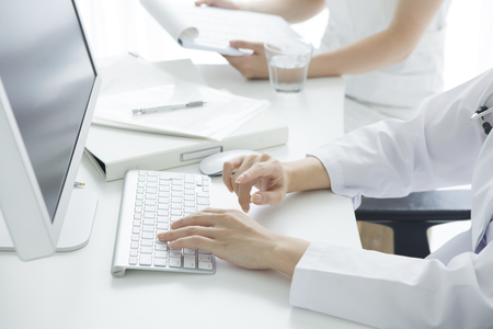 Doctor working at the hospital uses a personal computer 스톡 콘텐츠