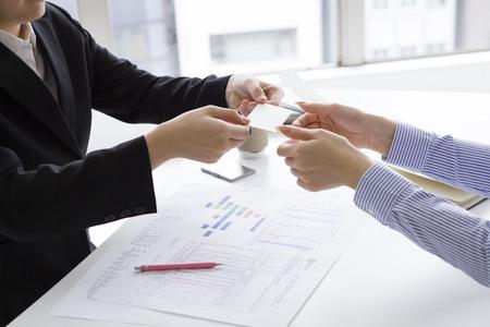 2 つのアジアのビジネス女性が名刺交換を持っています。