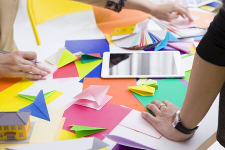 two people only: There are a lot of colorful origami on the desk