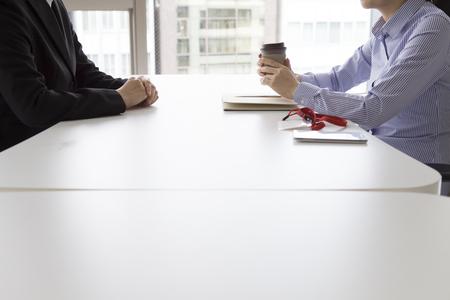contrato de trabajo: La empresaria tiene una entrevista en la oficina de la cara a cara con una taza de café