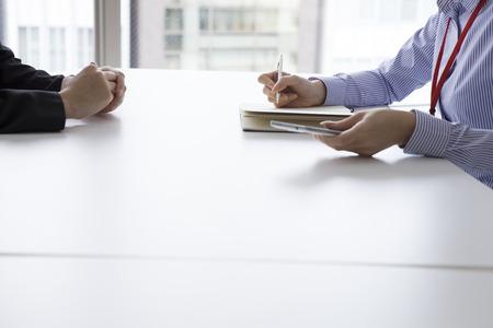 entrevista de trabajo: La empresaria tiene una entrevista en la oficina de la cara a cara mientras toma notas Foto de archivo