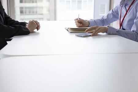 D'affaires ont une interview dans le visage de bureau à face en prenant des notes