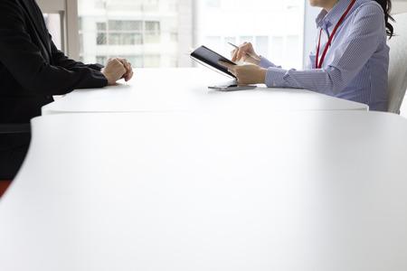Geschäftsfrau haben die Geschichte der Frau im Büro Gesicht gehört zu stellen und gleichzeitig Notizen Standard-Bild