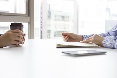 Empresaria realización de una entrevista de trabajo sentado en su escritorio en su oficina en el potencial candidata