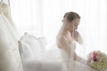結婚式: 花嫁は待っている部屋で指に添付されている結婚指輪にキスをしました。 写真素材