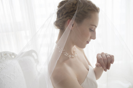 Bride wearing a wedding dress is staring at the wedding ring Stock Photo