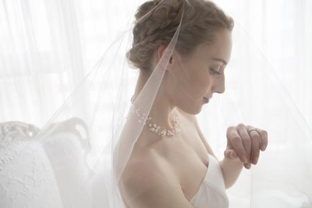 Bruid draagt een trouwjurk is staren naar de trouwring Stockfoto
