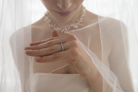 ring stand: Bride wearing a wedding dress is staring at the wedding ring Stock Photo