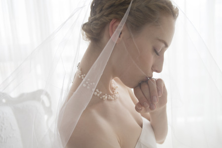 cérémonie mariage: Beautiful bride with a kiss on the wedding ring that is attached to the hand