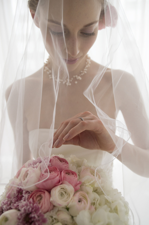 Beautiful bride is staring at the wedding ring that is attached to the hand