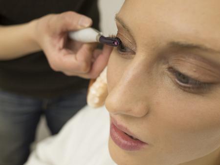 makeup artists: Make-up artists are curled eyelashes female models Stock Photo