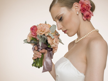 Portrait of beautiful newlywed with wedding bouquet of flowers