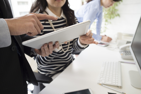 Businessmen and business women looking at a tablet together