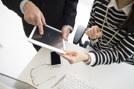 co work: Businessmen and business women looking at a tablet together