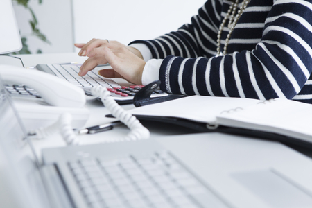 Business woman is type in the PC at the desk