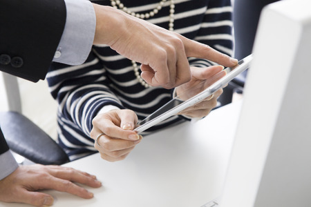 co work: Businessmen and women looking at a tablet together