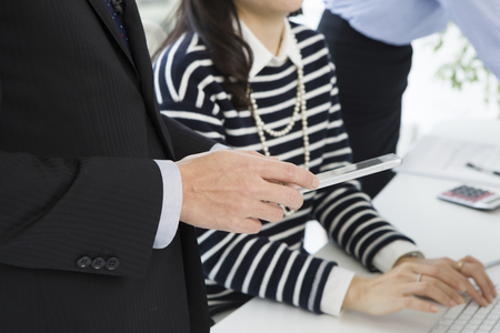 co work: Women are entering the PC while talking with businessman Stock Photo