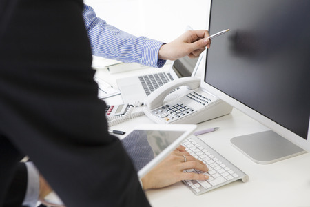 Woman is pointing to the screen of the desktop with a pen