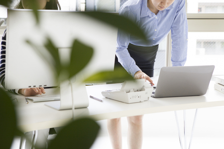 Woman is using a laptop standing in the office