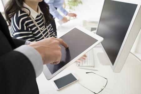 co work: Businessman is touching the screen of the electronic tablet