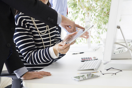 co work: Woman is showing a tablet to men businessman