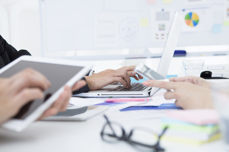co work: Business women are using electronic tablet in a meeting Stock Photo