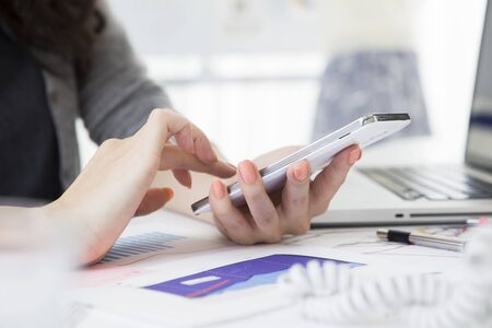 markerboard: Business woman looking at the mobile phone in the office Stock Photo